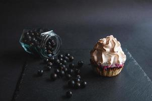 Appetizing baked vanilla muffin with currants on a black photo