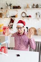 Hombre con gorro de Papá Noel saludando a sus amigos en video chat o llamada en tableta foto
