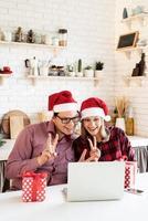 Pareja con gorro de Papá Noel saludando a sus amigos en una videollamada foto