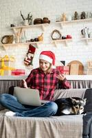Woman in santa hat greeting her friends in video chat on laptop photo