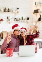 Couple in santa hats greeting their friends in a video call photo