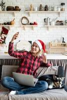 Young woman in santa hat greeting her friends in video chat on laptop photo