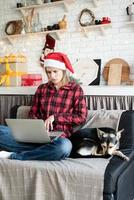 Young blonde woman in santa hat working on laptop photo