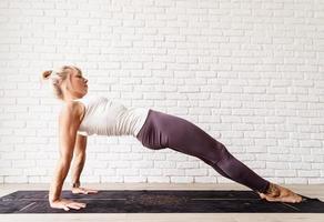 Blonde woman practising yoga at home, doing glute bridge photo