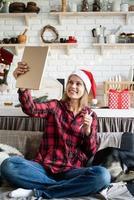Joven mujer rubia con gorro de Papá Noel trabajando en tableta sentado en el sofá foto