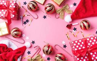 Top view of Christmas and New Year decorations with confetti, gift boxes and santa hats on pink background flat lay photo