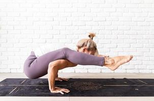 Blonde woman practising yoga at home, making exercises on the mat photo