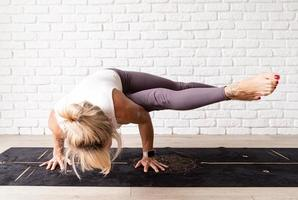 Blonde woman practising yoga at home photo