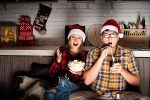 Couple watching movies at home at Christmas pointing to the screen photo