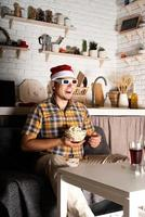 Young man in 3D glasses watching movies at home at night at Christmas photo
