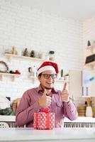 Hombre con gorro de Papá Noel saludando a sus amigos en video chat en tableta foto