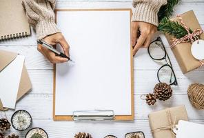 A hand holding a pen to write on a clipboard photo