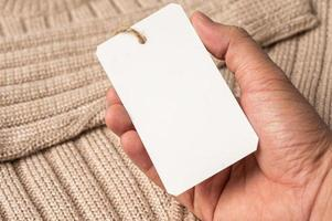 A hand holding a white tag on a brown sweater photo