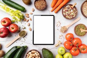 Top view of a tablet with white screen for mock up with healthy foods photo