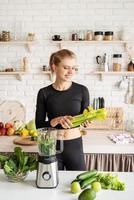 Joven mujer sonriente rubia haciendo batido de apio en la cocina de casa foto
