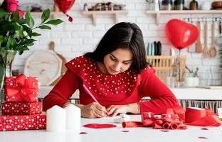 Woman  writing love letter sitting at the decorated kitchen photo