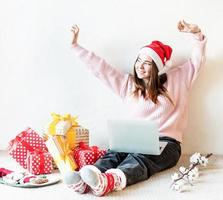 Young woman in santa hat shopping online surrounded by presents photo