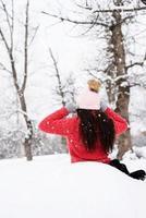 Vista trasera de una mujer morena sentada en el parque cubierto de nieve en la nieve foto