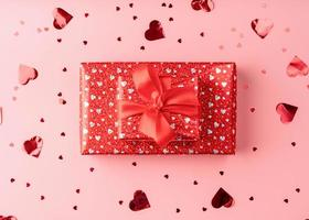 Red gift box with rope bow on pink background with heart confetti photo