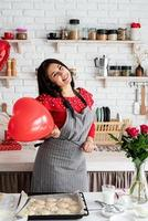 Woman in red dress and gray apron holding red heart balloon photo