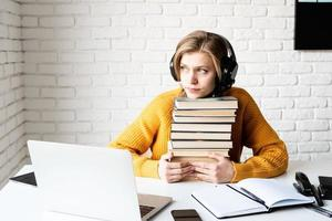 mujer joven, estudiar, en línea, tenencia, un, pila de libros foto