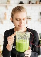 Young blond smiling woman making green smoothie at home kitchen photo