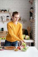 Hermosa joven preparando ensalada griega en la cocina cortando lechuga foto