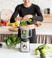 Joven mujer sonriente rubia haciendo batido de espinacas en la cocina de casa foto