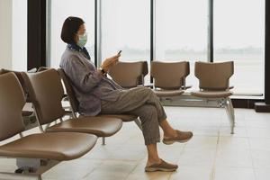 Masked woman sitting in airport photo