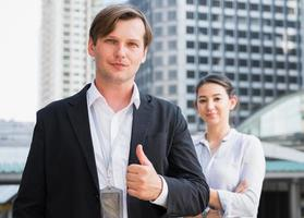 Portrait team of businessman and woman showing thumbs up photo