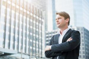 Businessman standing with arms crossed on business building background photo