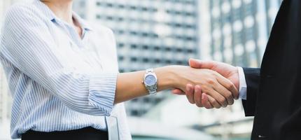 hombres y mujeres de negocios dándose la mano foto