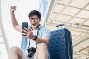 Asian traveler man is happy while looking at smartphone photo