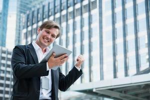 Young business man feeling happy holding tablet photo