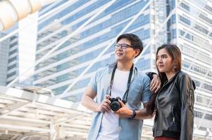 turista de pareja asiática mirando hacia adelante y viajar en la ciudad urbana. foto