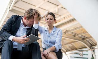 Portrait of businessman and woman looking at tablet and feels sad photo