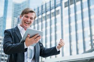 hombre de negocios joven que se siente feliz sosteniendo la tableta foto