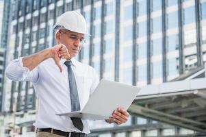 Ingeniería civil usando laptop mientras trabaja en la construcción foto