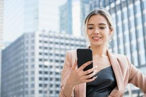 Portrait of smiling pretty young business woman using phone photo