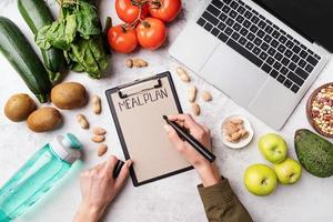 Female hands writing in the notepad words meal plan, top view flat lay photo