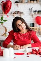 Mujer escribiendo una carta de amor sentada en la cocina decorada foto