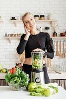 Mujer haciendo batido verde en la cocina de casa foto
