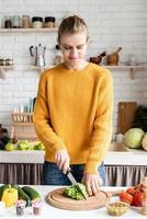 Bella mujer preparando ensalada griega en la cocina foto