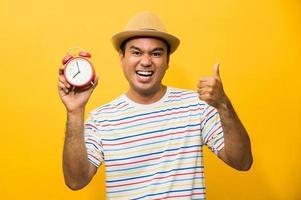 joven asiático sosteniendo el despertador sobre fondo amarillo aislado. foto