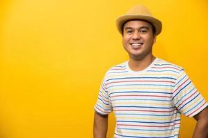 joven apuesto hombre asiático sobre fondo amarillo. foto
