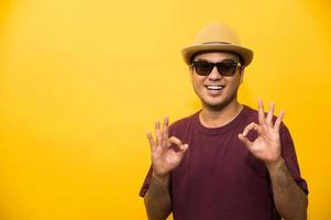 Young asian man showing hand ok sign on yellow background. photo