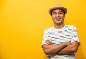joven apuesto hombre asiático con el brazo cruzado sobre fondo amarillo. foto