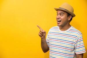joven, feliz, divertido, asiático, hombre, señalar con el dedo, en, espacio en blanco foto