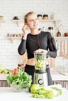 Woman making green smoothie at home kitchen photo