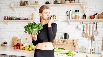 Woman in sport clothes holding a bowl of fresh spinach in the kitchen photo